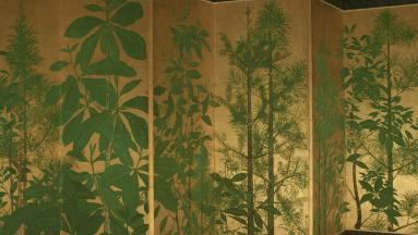 This is an image of a folding screen featuring paintings of various green plants and trees set against a gold background.