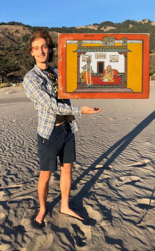 In this photomontage, a smiling young man stands on a beach on a sunny day. His hand appears to hold up a painting of a domestic scene framed in bright orange and yellow.