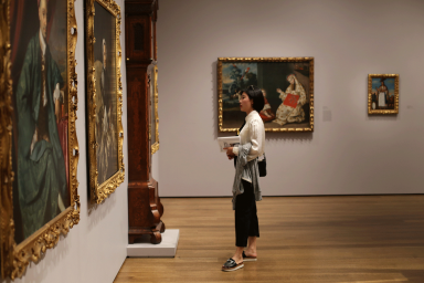 A woman in profile wearing a white blouse and black pants gazes at a painting with an ornate gold frame in a gallery. On the surrounding walls, there are many other paintings with similar ornate gold frames as well as a long case musical clock.