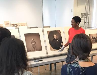 A woman gestures toward photographs displayed on a long table, with four people listening on in the foreground.