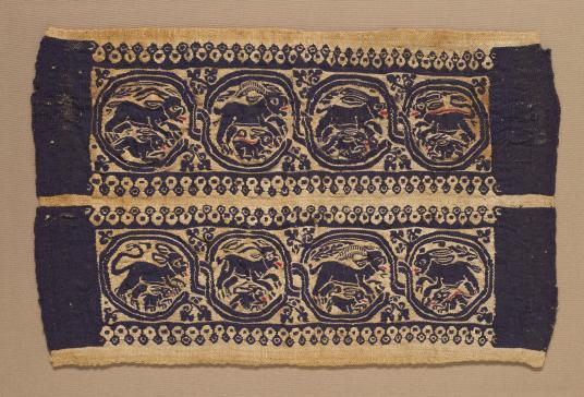 A rectangular textile fragment that features four roundels with animals.