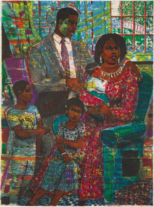 A woman holding a child is seated on an easy chair in a living room with her family gathered around her.