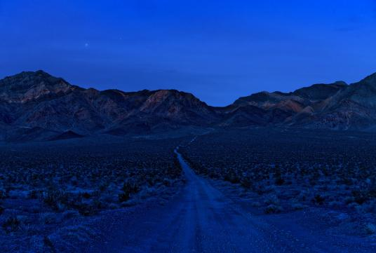 A blue-saturated photograph of a desert landscape at night with a winding road in the foreground and mountains in the background.