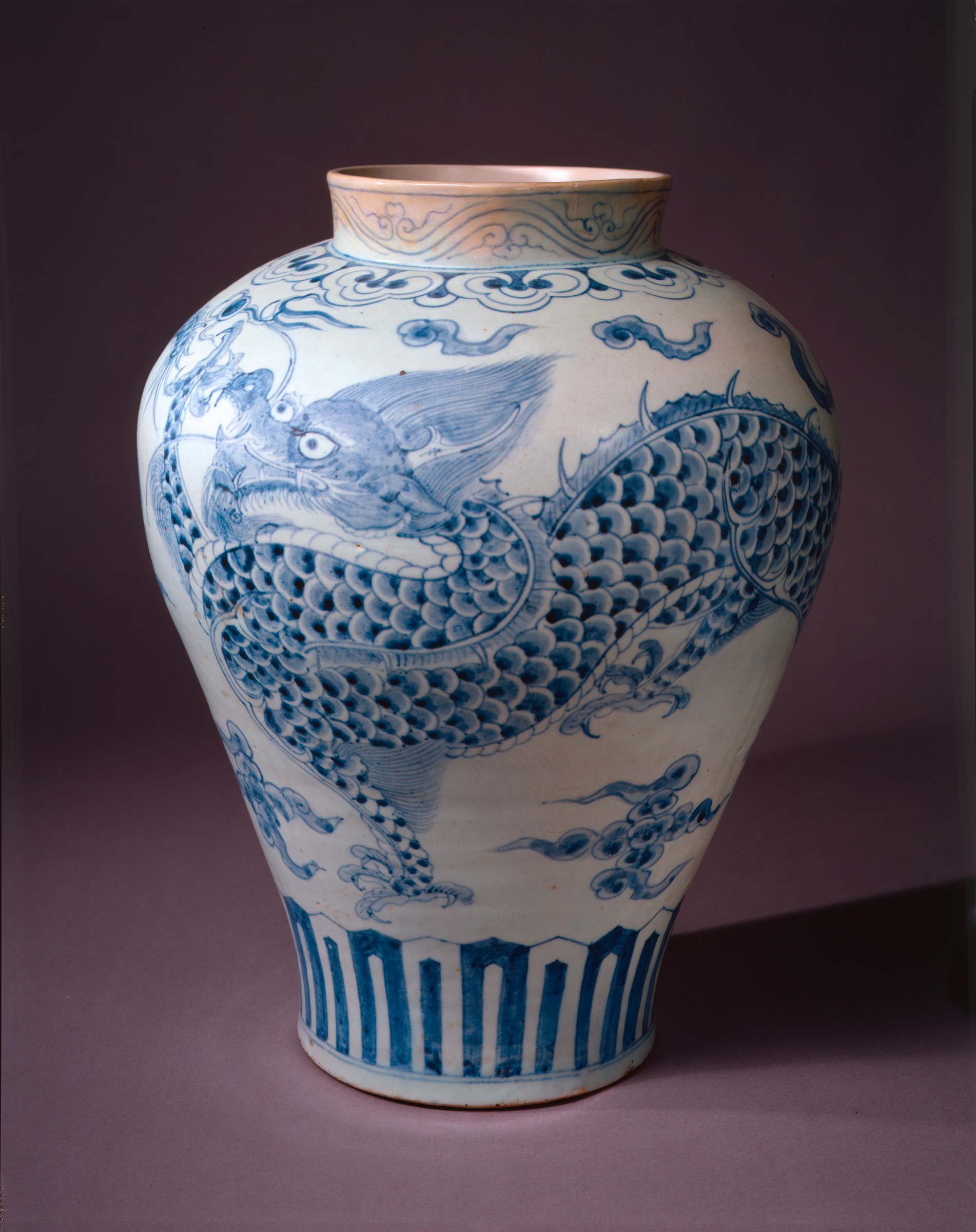 Large white jar with broad shoulders. Two blue dragons wrap around the outside of the jar, each grasping at a flaming jewel, also in blue.