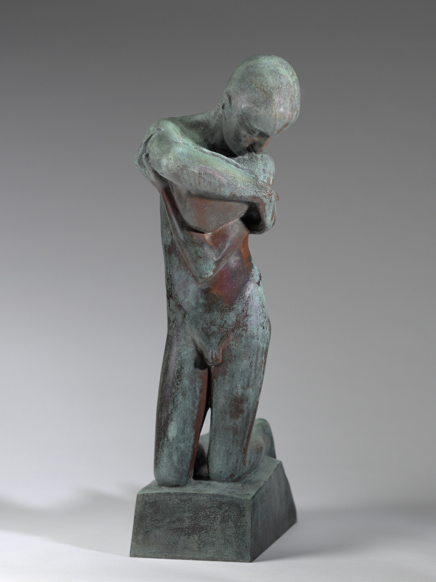 An abstract bronze sculpture of a human figure kneeling and cradling a shell