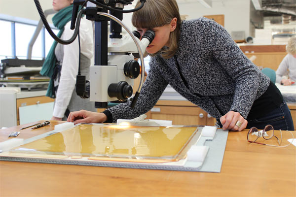 Curatorial fellow Maja Wismer examines Beuys's Phosphorus-Cross Sled through a microscope in the Straus Center's conservation lab.