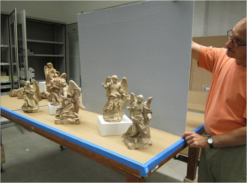 Preparator Steve Mikulka holds the backboard for the mock-up of a display case for Bernini's terracotta sculptures.