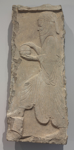 Servant with Covered Bowl, Achaemenid Persian, c. 359–338 BCE. Limestone relief. Harvard Art Museums/Arthur M. Sackler Museum, Bequest of Grenville L. Winthrop, 1943.1311.