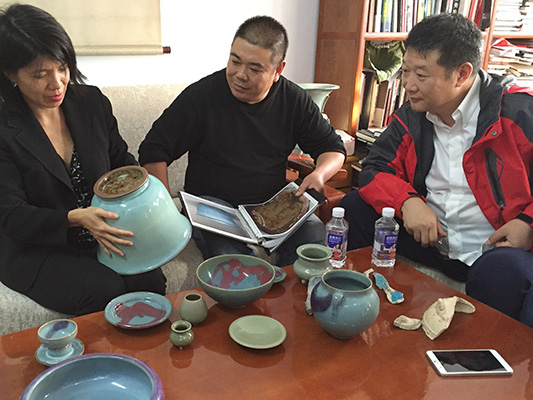 Melissa Moy and artists Liu Zhijun (center) and Zhao Meng examine modern-day replicas of numbered Jun ware.