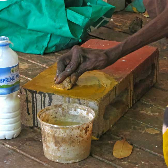Our team observed artists as they worked in Yirrkala. Artist Nyapanyapa Yunupingu grinds ochre into pigment and mixes it with a polyvinyl acetate binding medium in the water bottle, in preparation for painting Photo: Narayan Khandekar.