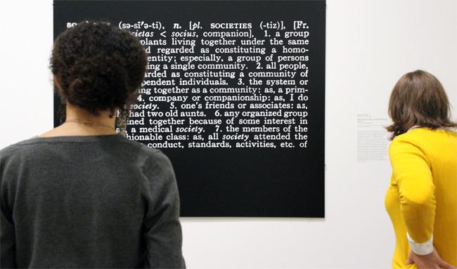 Students gather around Joseph Kosuth's Titled (Art as Idea as Idea), [Society], 20th century. Photostat mounted on board. © 2015 Joseph Kosuth/Artists Rights Society (ARS), New York.