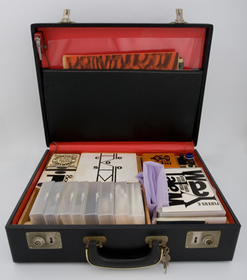 Various artists, designed and edited by George Maciunas, Flux-Kit, 1964. Vinyl briefcase, title silkscreened on lid, containing numerous Fluxus editions. Harvard Art Museums/Fogg Museum, Barbara and Peter Moore Fluxus Collection, Margaret Fisher Fund and gift of Barbara Moore/Bound & Unbound, M26446. © George Maciunas Foundation.