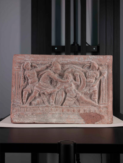 The bottom part of the Etruscan urn depicting the battle scene, shown in natural light.
