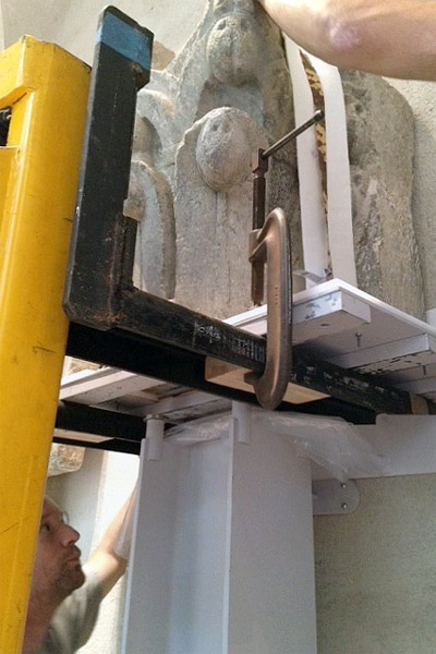 The complex process of installation was the result of months of testing. Here a capital is on a pallet, secured via the safeguard mount above the capital. The pallet piece was then separated and removed, leaving the heavy stone art to stand freely on the I-beam.