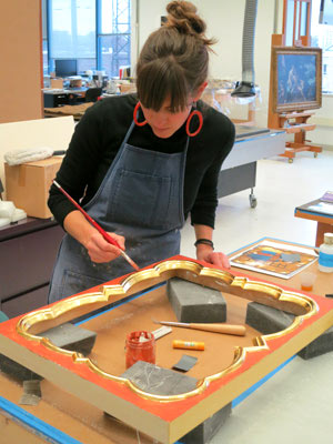 Frame conservator Allison Jackson applies red bole to the frieze after gilding the inner molding.
