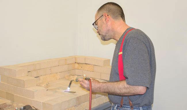 Peter Schilling anneals a brass mount part, a process that softens the metal.