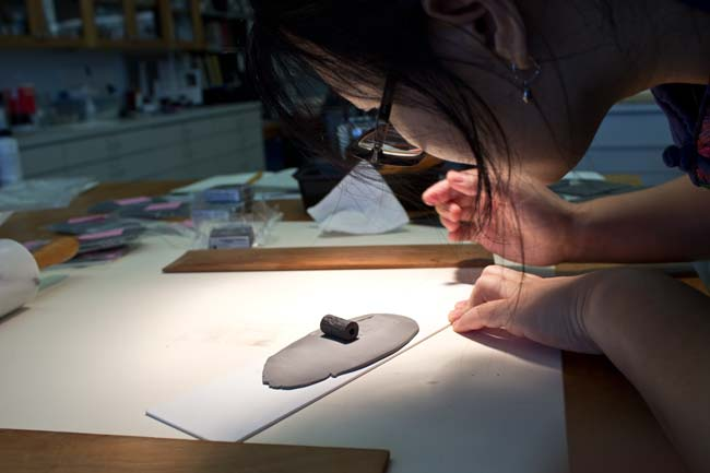 Yan Jia rolls a cylinder seal on the clay surface to create an impression, known as a sealing.