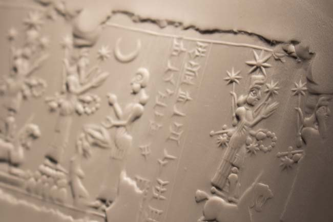 Impression of a cylinder seal depicting deities and a worshipper.