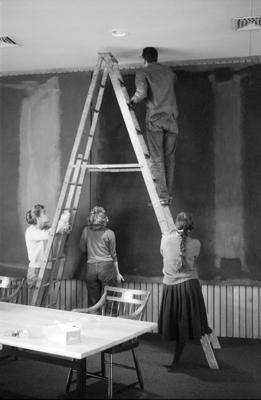 Conservators Rhoda Burden, Jean Lampton (Woodward), Gregory Smyrlian, and Marjorie Cohn install Panel Two of the Harvard Murals, Holyoke Center, January 1963. Photo: Elizabeth H. Jones.