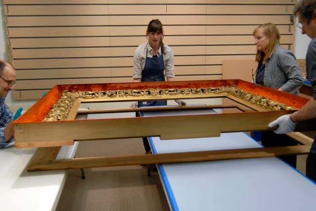 Conservators and collections management staff dismantle the painting's shadow-box frame.