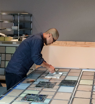 Takuji Hamanaka, who works with stained-glass conservator Mary Clerkin Higgins, mounts stained-glass panels into one of the windows in the Naumburg Room.