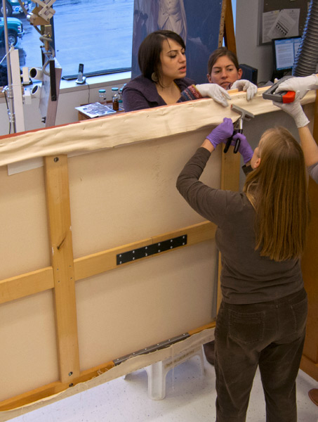 Conservators Dina Anchin, Allison Jackson, and Teri Hensick stretch the canvas in our Straus Center. Photo: Straus Center staff.