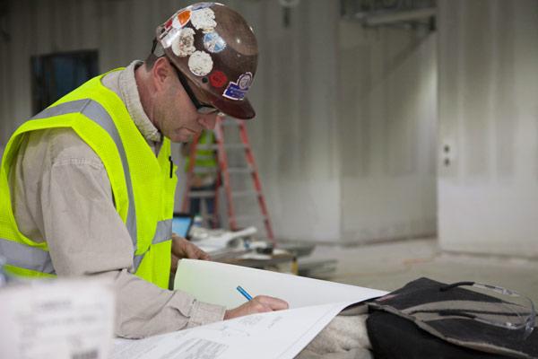 General foreman Tom Frazier looks over building plans. Photo: Peter Vanderwarker.