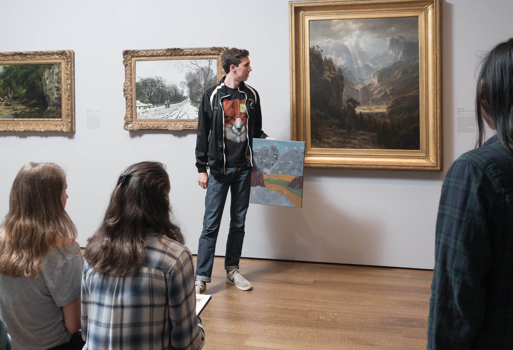"A CRLS student presents his final project in front of Albert Bierstadt's  ""Rocky Mountains, 'Lander's Peak.'"" Photo by Matthew Monteith."