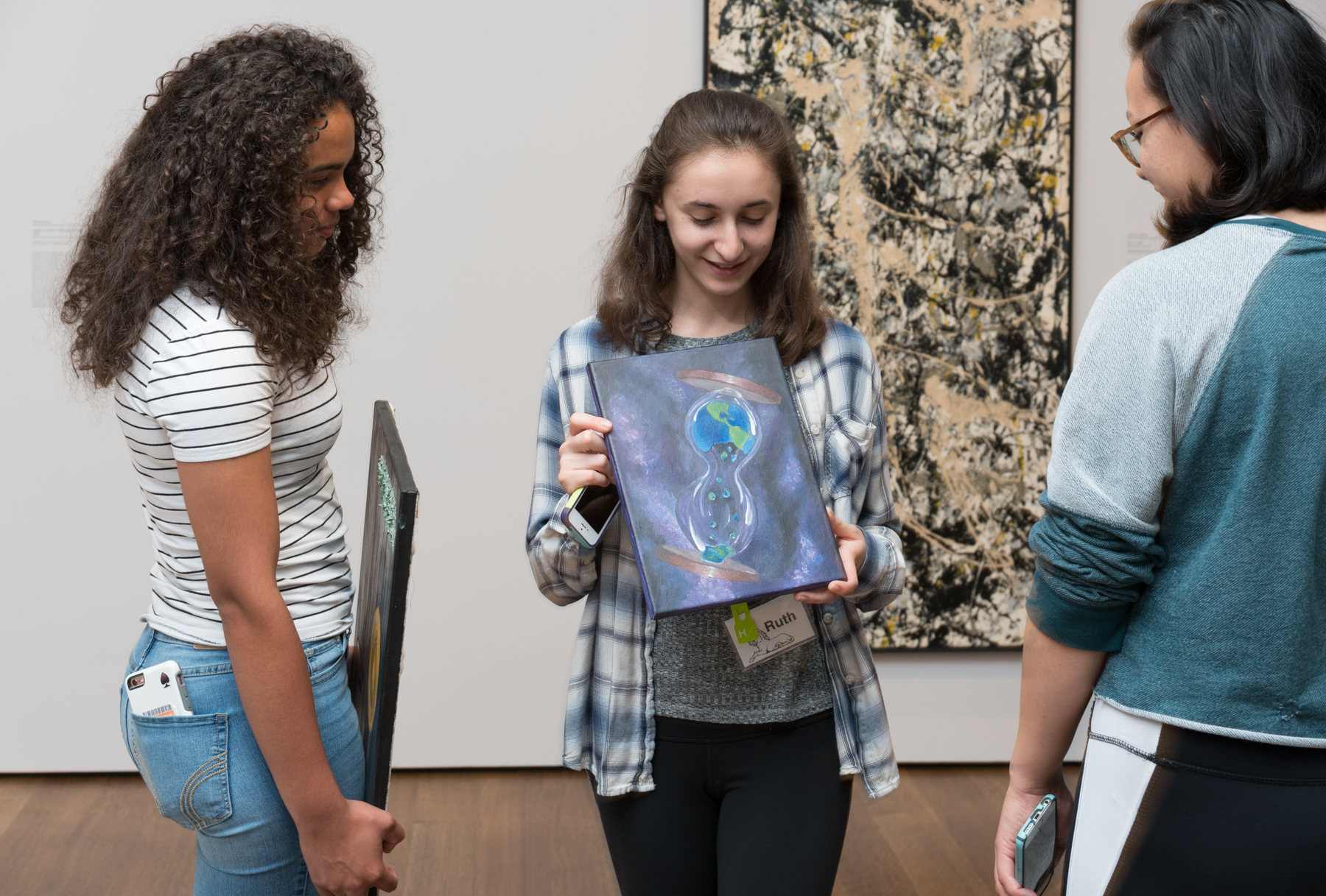 For their final projects, the CRLS students presented their original creations in front of the artwork that inspired them. Here, Ruth Albert-Lyons, a CRLS junior, displays her painting inspired by environmental issues. Photo by Matthew Monteith.