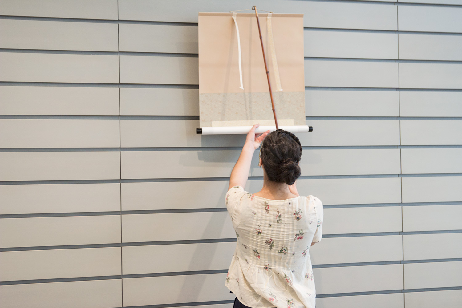 Sirrine unrolls a hanging scroll on the wall of an Art Study Center seminar room, in preparation for a visitor appointment.