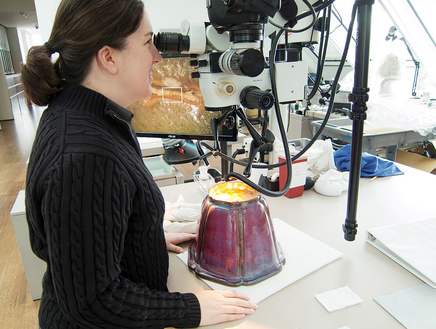 Costello examines a numbered Jun vessel under a microscope.