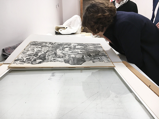 Austėja Mackelaitė examines a collage by Jean Dubuffet at Sotheby's Paris.