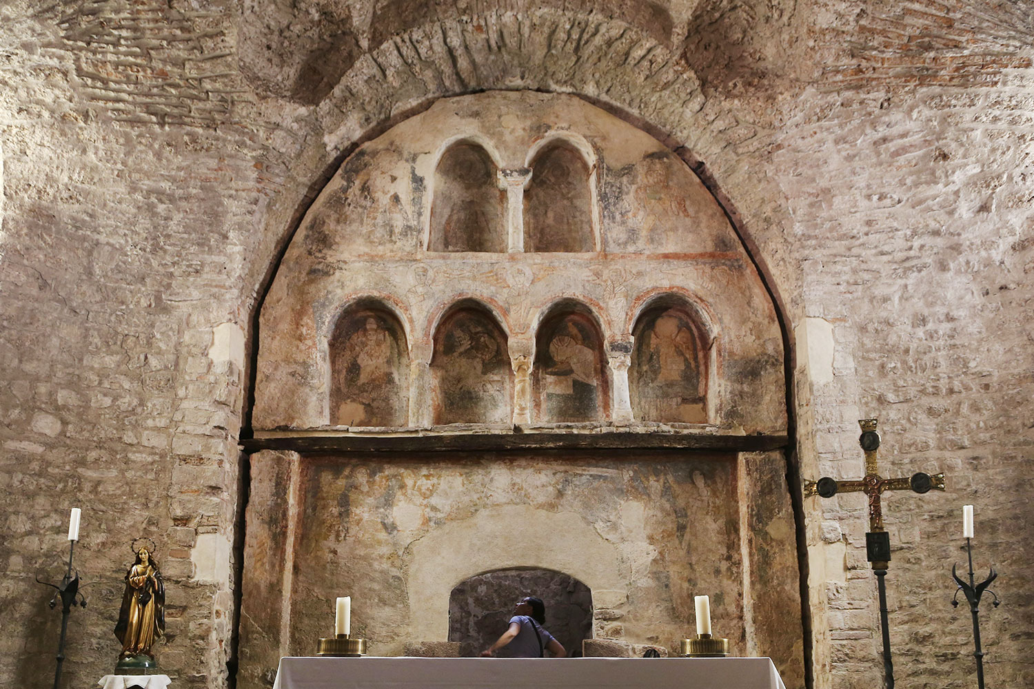 Borrassà's altarpiece would have hung over these Romanesque frescoes, which had gone out of style by the 15th century. The museums' panel was located behind the candle that sits on the right half of the table.