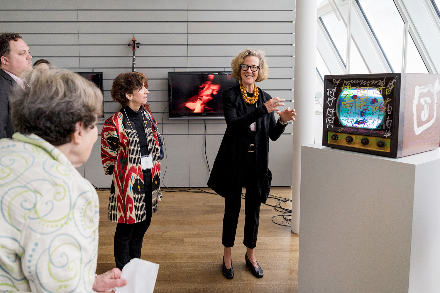 Mary Schneider Enriquez, right, the Houghton Associate Curator of Modern and Contemporary Art, discusses a work by Nam June Paik with visitors. A recent gift of approximately 10 works by Paik will enhance the study of mid-20th-century art, video art, and related subjects.