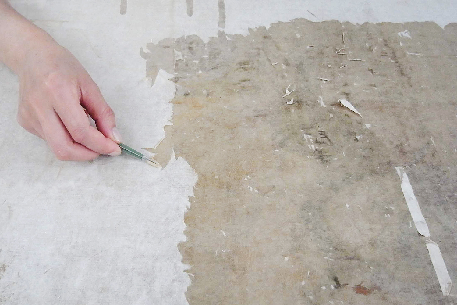 A conservator at the Handa Kyuseido studio in Japan carefully removes layers of backing paper from one of the paintings.