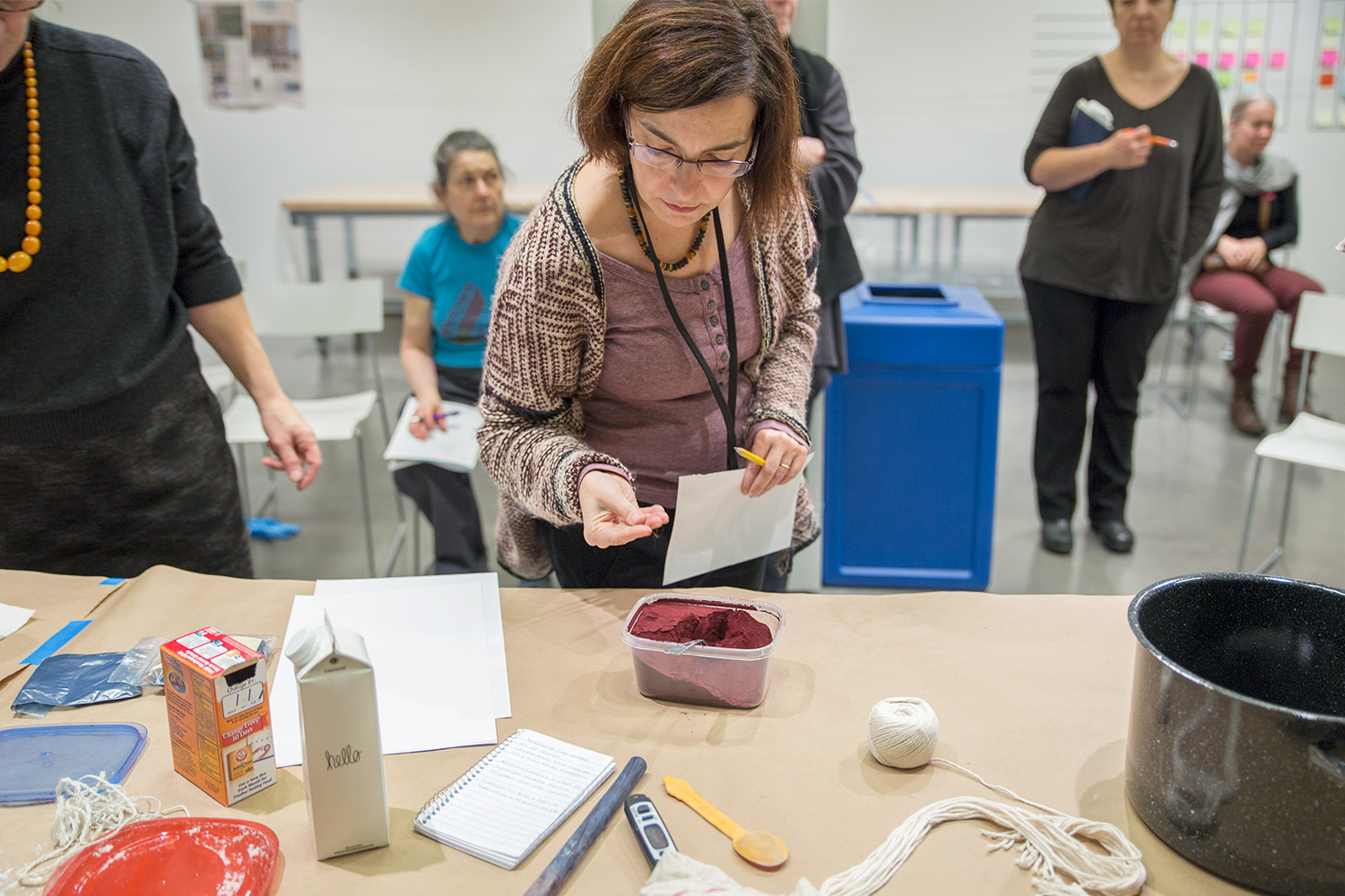 A workshop participant takes a close look at the powdered cochineal.