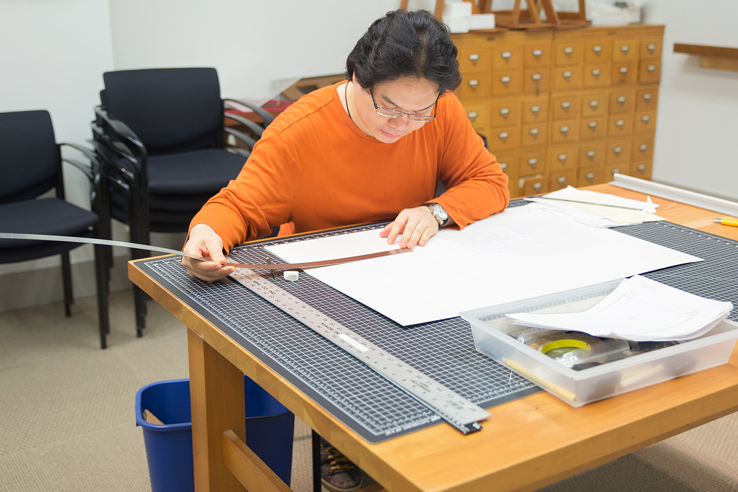 A student makes measurements on archival corrugated board as the first step in building a custom box for storage.