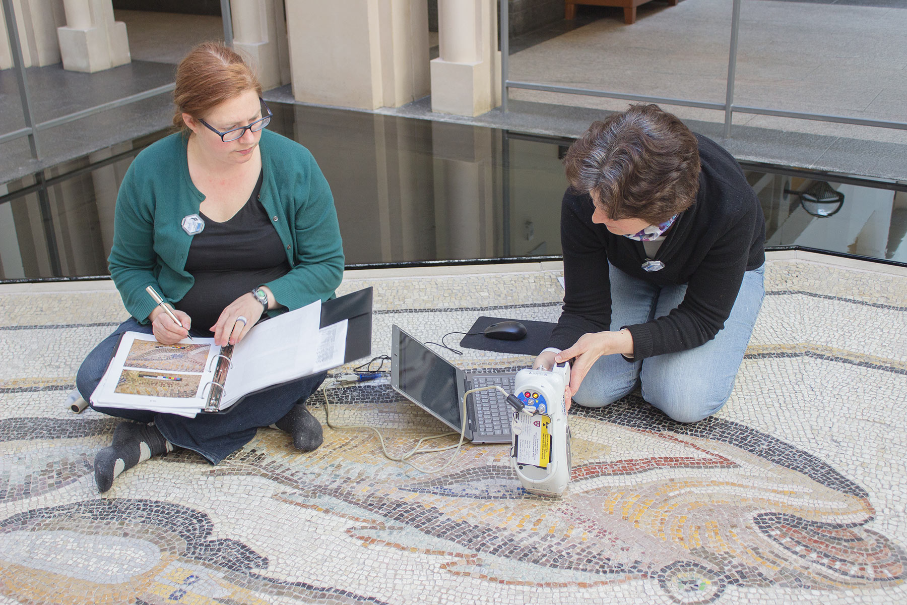 Elizabeth LaDuc, left, of University College London and former fellow in the objects lab of the Straus Center for Conservation and Technical Studies, and Katherine Eremin, the Patricia Cornwell Senior Conservation Scientist in the Straus Center, use a handheld XRF scanner to study the tesserae in the mosaic.