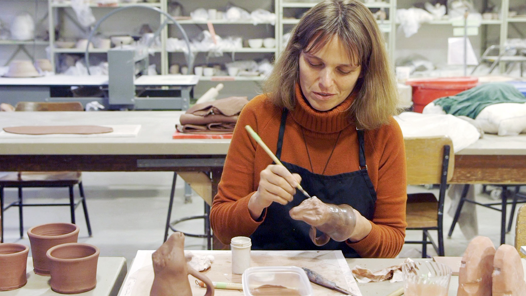 Susanne Ebbinghaus, the George M.A. Hanfmann Curator of Ancient Art, applies glaze to her version of an ancient ram-shaped vessel.