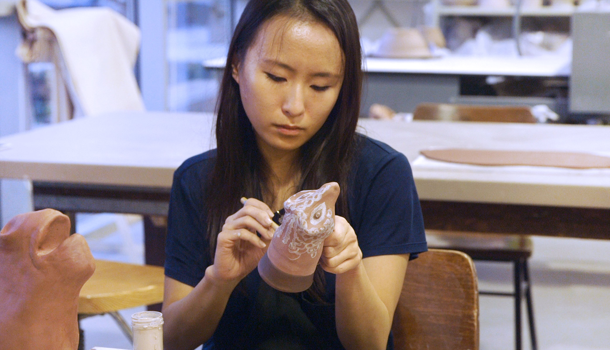 Anjie Liu applies glaze to a clay object, a reproduction of a ram-shaped vessel.
