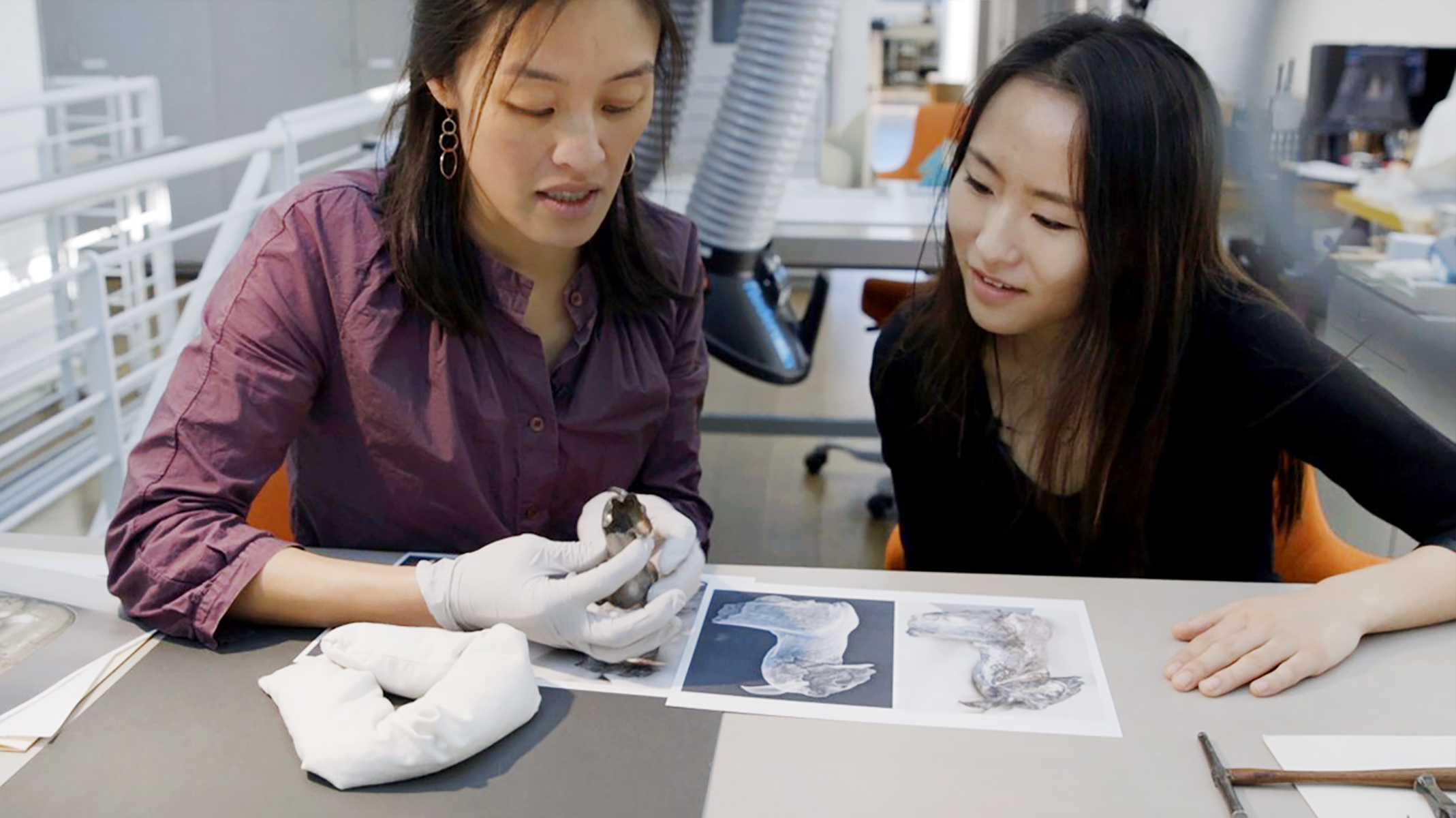 Angela Chang, left, and Anjie Liu examine a fragment of a silver doe-shaped rhyton. On the table in front of them are X-ray images of the same object.