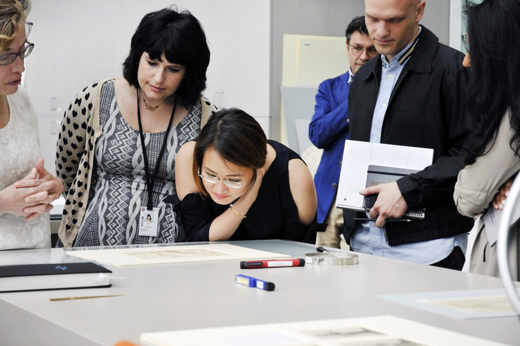 Christine Zapella, left, Cabelle Ahn, center, and Ian Wallace, each of whom participated in the 2017 session, examine a drawing in the paper lab of the Straus Center for Conservation and Technical Studies.