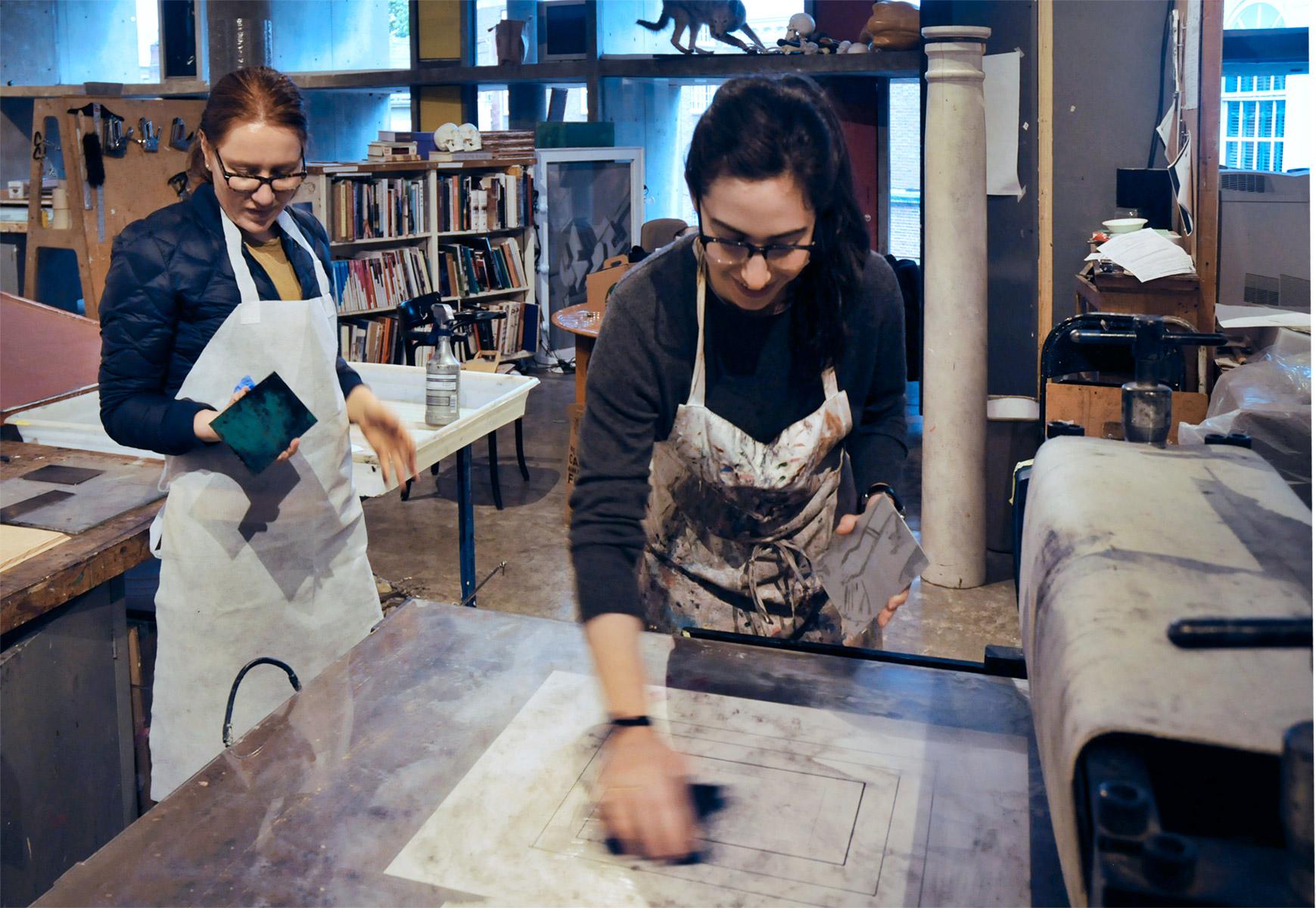 Kathryn Kremnitzer and Michal Goldschmidt prepare to print their etchings during Matt Saunders's printmaking session.