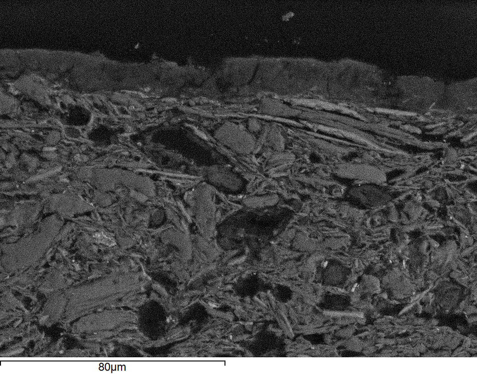 A magnified detail of the jar's surface, obtained through scanning electron microscopy, reveals a layer of manganese atop the terracotta.