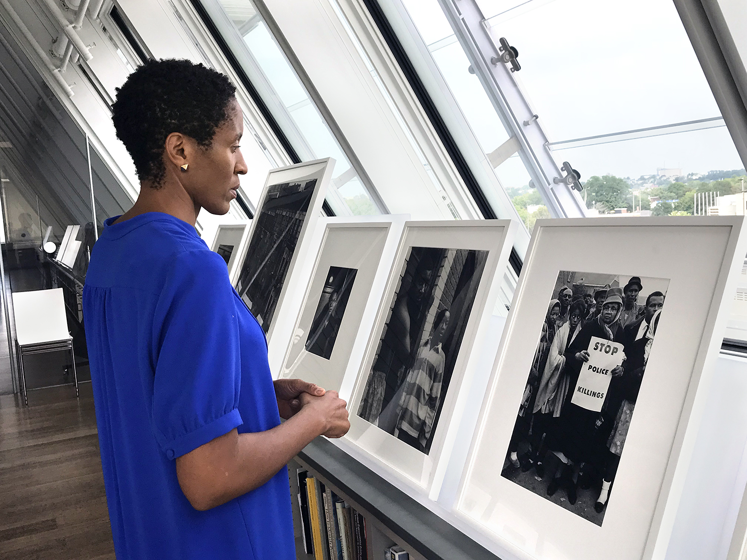 Makeda Best, the Harvard Art Museums' Richard L. Menschel Curator of Photography, views photographs, including Steve Schapiro's Stop Police Killings, Selma (1965), far right, in the Harvard Art Museums' Art Study Center, before they are installed in the exhibition Time is Now: Photography and Social Change in James Baldwin's America.
