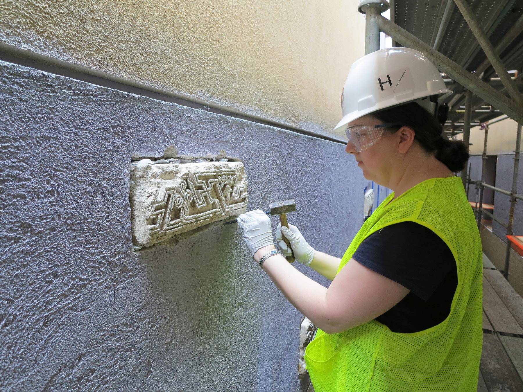 Susan Costello, associate conservator of objects and sculpture in the Straus Center for Conservation and Technical Studies, removes original sixth-century Coptic architectural fragments from the wall in Harvard's Arthur M. Sackler Building. As the building underwent renovations, a small team of conservators, curators, and tradespeople devised a plan to remove the fragile, very heavy original objects from the walls and replace them with 3D-printed reproductions.