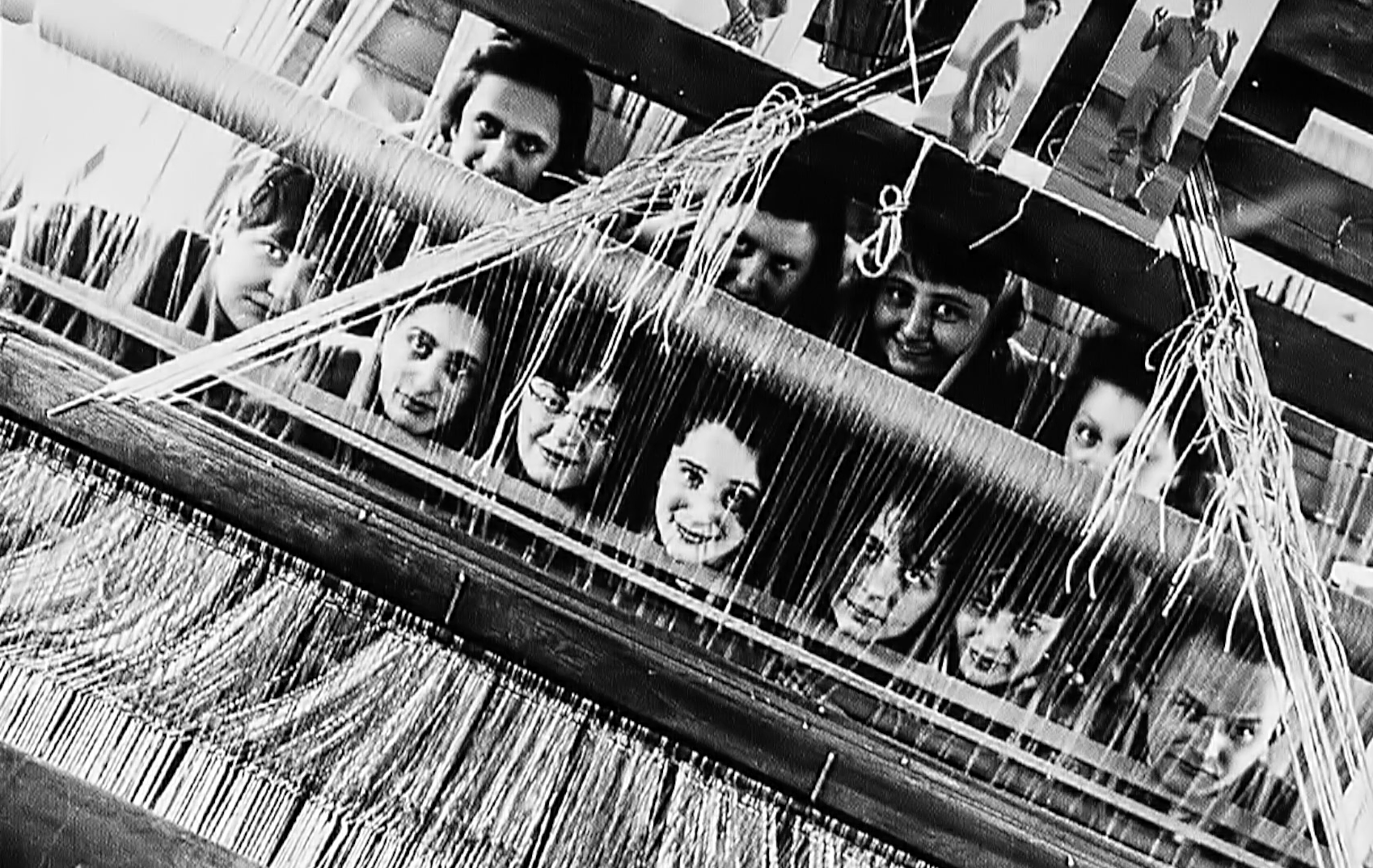 A video still featuring 11 women's faces peering out from behind a weaving loom at the Bauhaus.