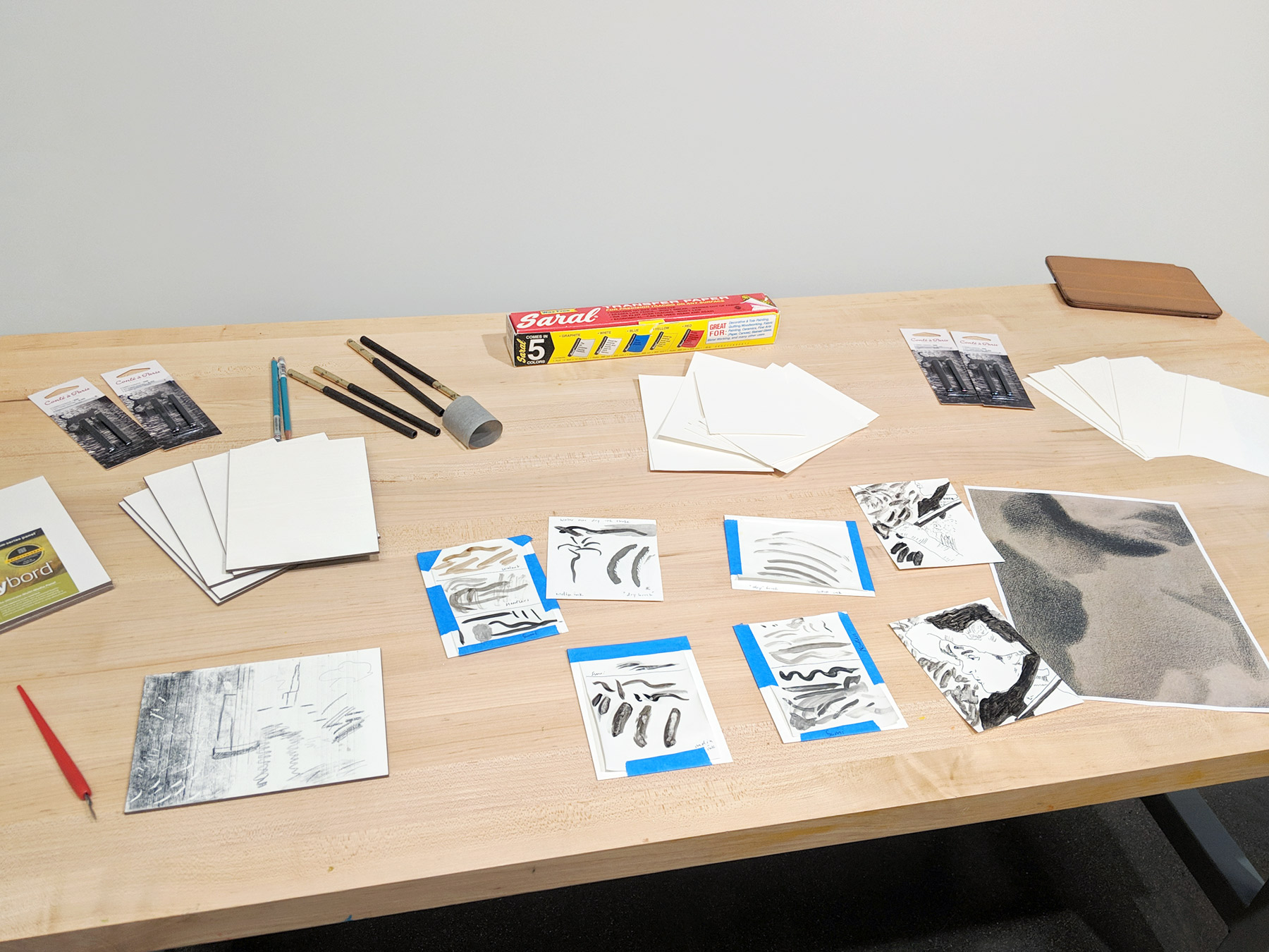 A table with a number of tools, materials, and test copies.