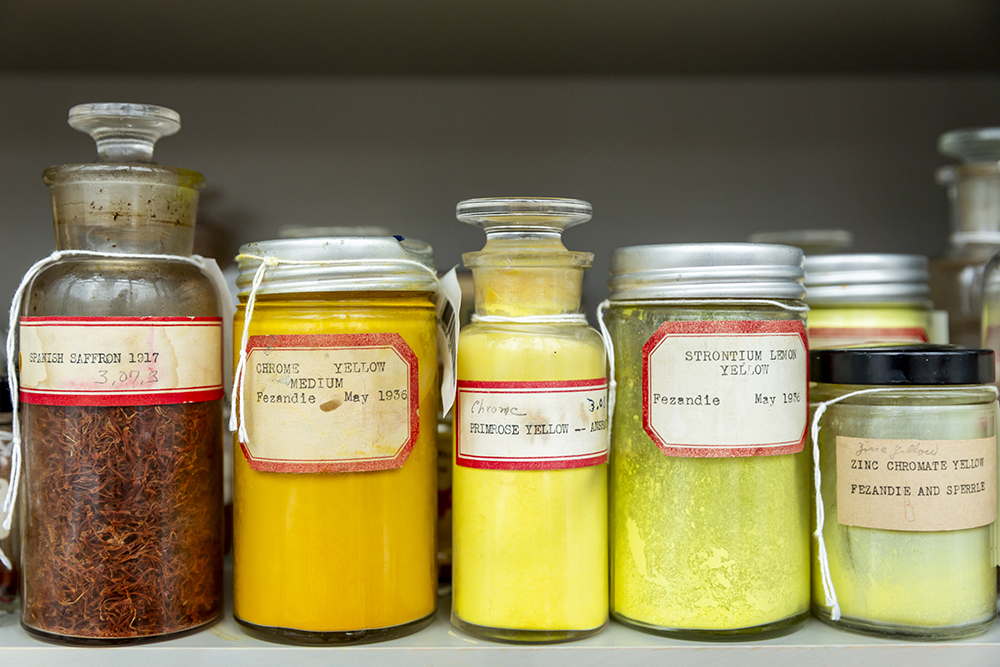 Five jars of pigments ranging in shades from a reddish-orange to a bright yellow lined on a shelf.