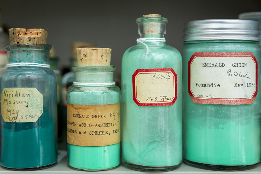 Four jars of aqua-colored pigments lined up next to one another in the cabinet.